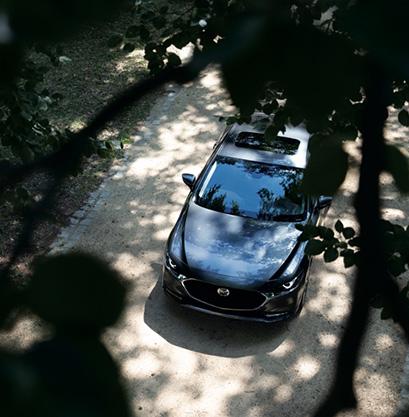 A peek of a Mazda3 Sedan through the trees