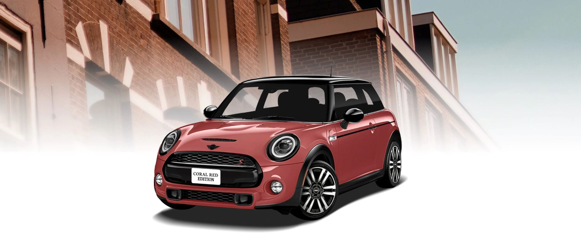 The MINI COOPER HARDTOP CORAL RED  EDITION in front of a brick building.
