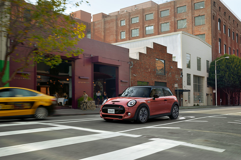 The MINI COOPER HARDTOP CORAL RED EDITION driving in the city.