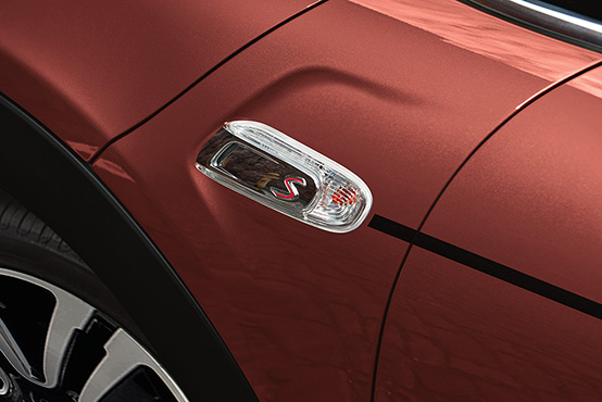 A close-up of the MINI COOPER HARDTOP CORAL RED EDITION's Coral Red Metallic exterior paint and Black Pinstripe.
