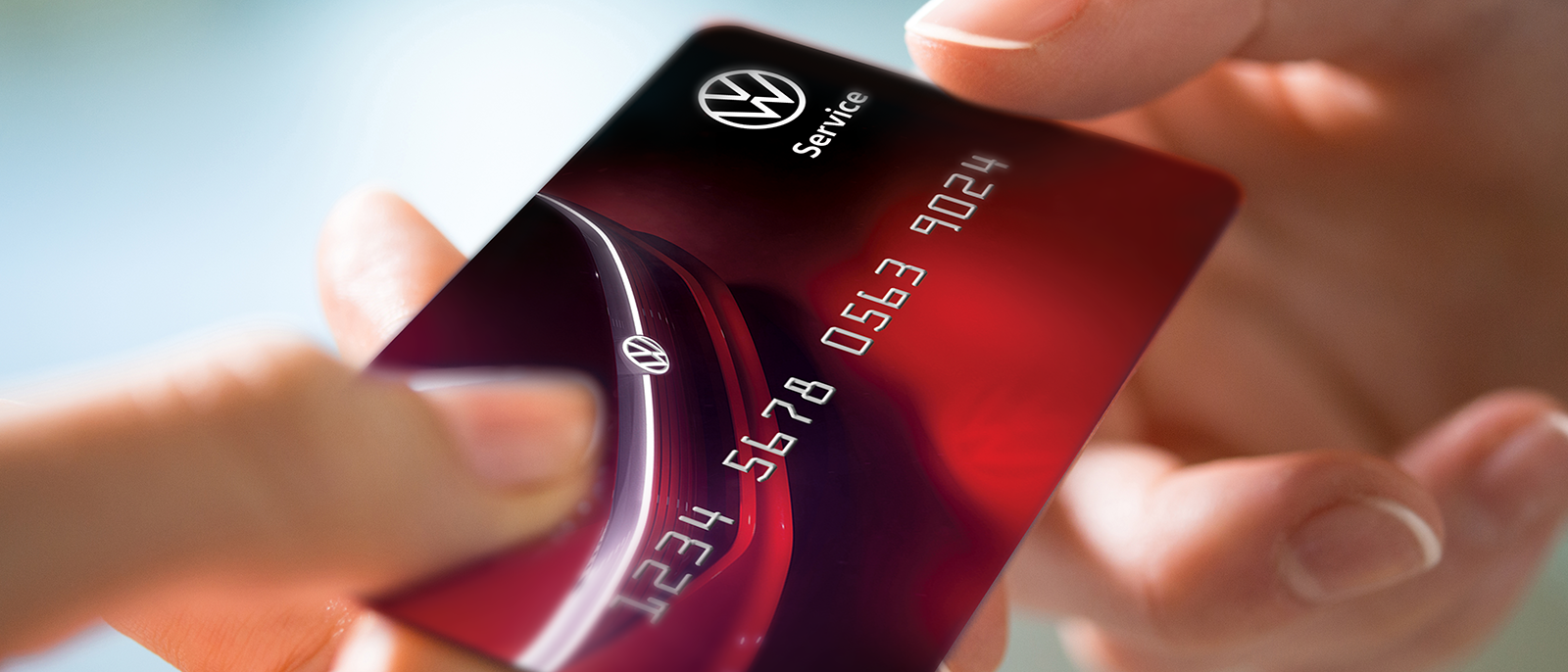 A person handing a Volkswagen service credit card
