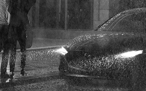 Mazda3 Sedan in the rain as a couple run towards it
