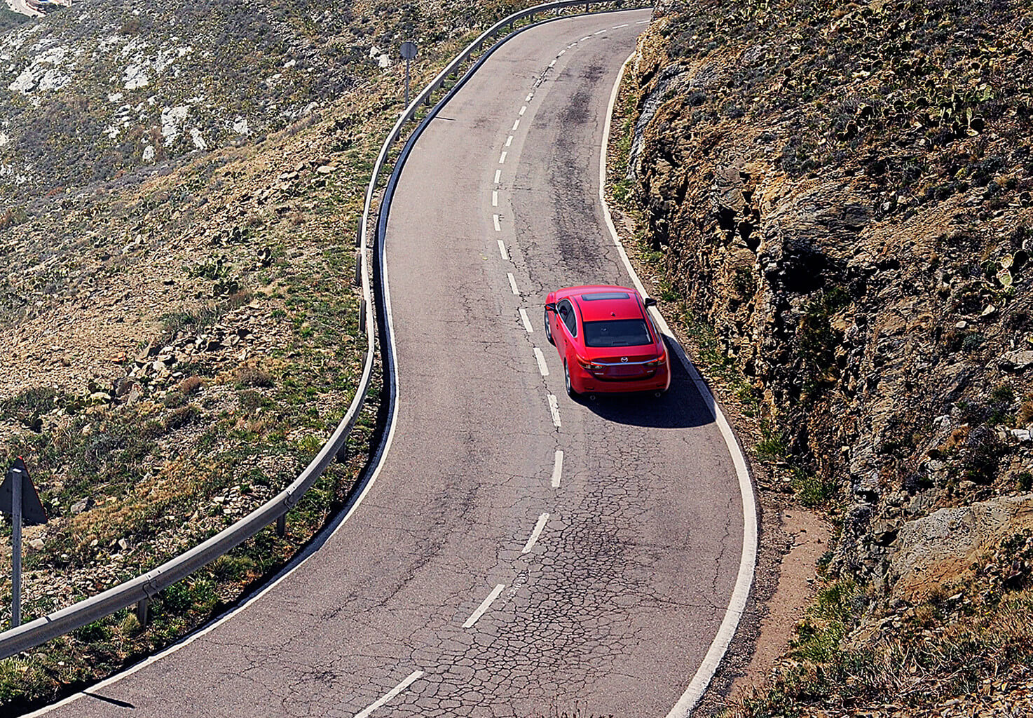 """A red Mazda making it""""s way up the road"""