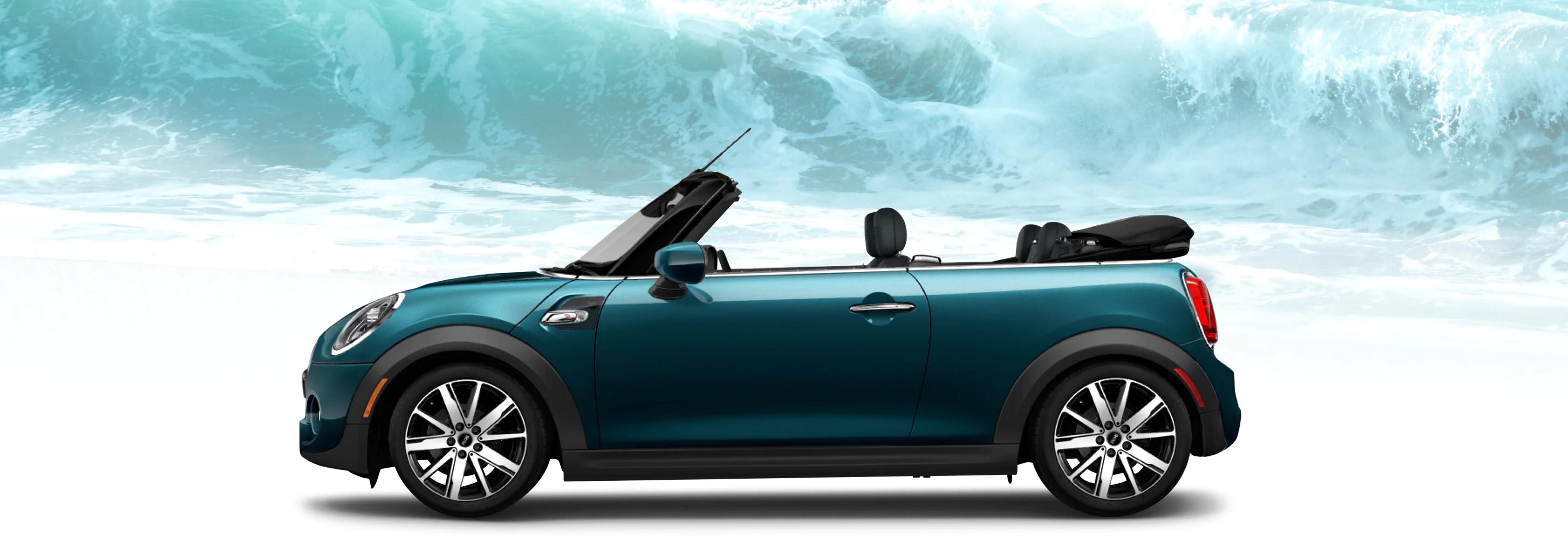 The MINI Cooper S Convertible Sidewalk Edition in front of a large ocean wave.
