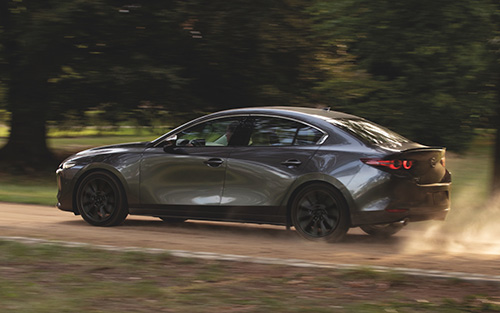 A gray Mazda3 driving on a dusty road