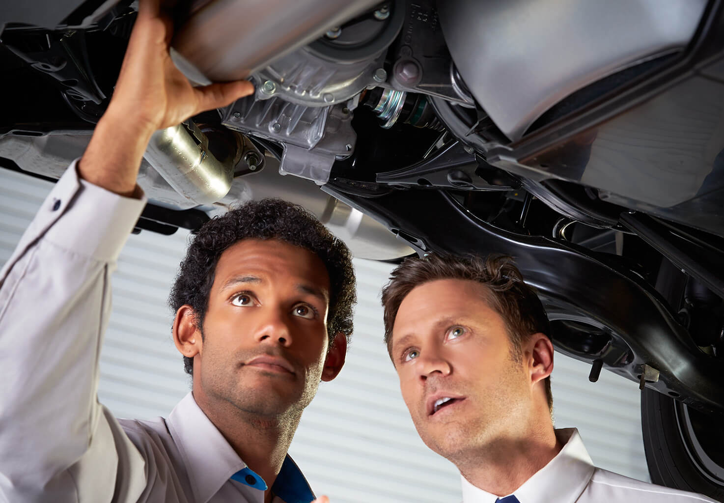 two men inspecting the workings of a car