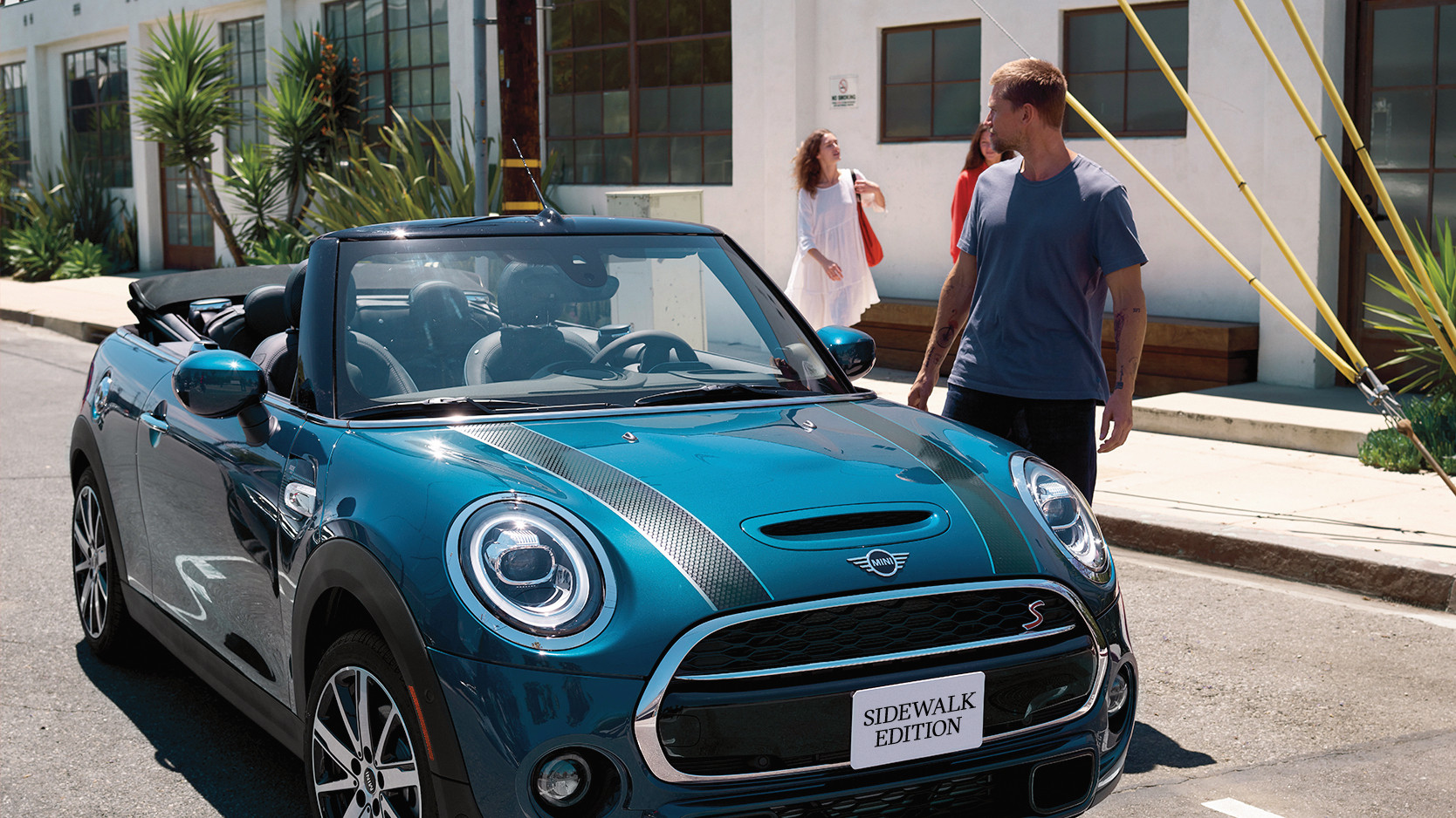 A man about to enter the MINI Cooper S Convertible Sidewalk Edition parked on the street.