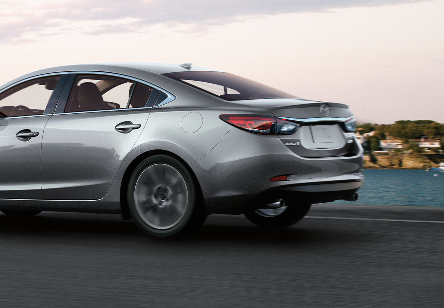 Silver Mazda6 going fast down the road