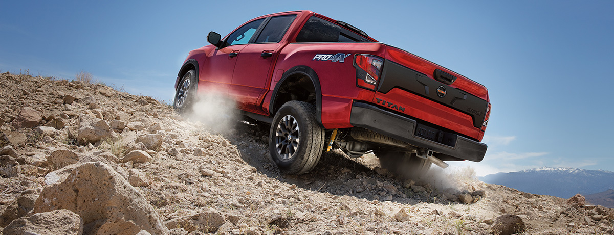 Red 2020 NIssan Titan driving up a rocky hill