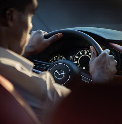 A man driving a Mazda3 Hatchback