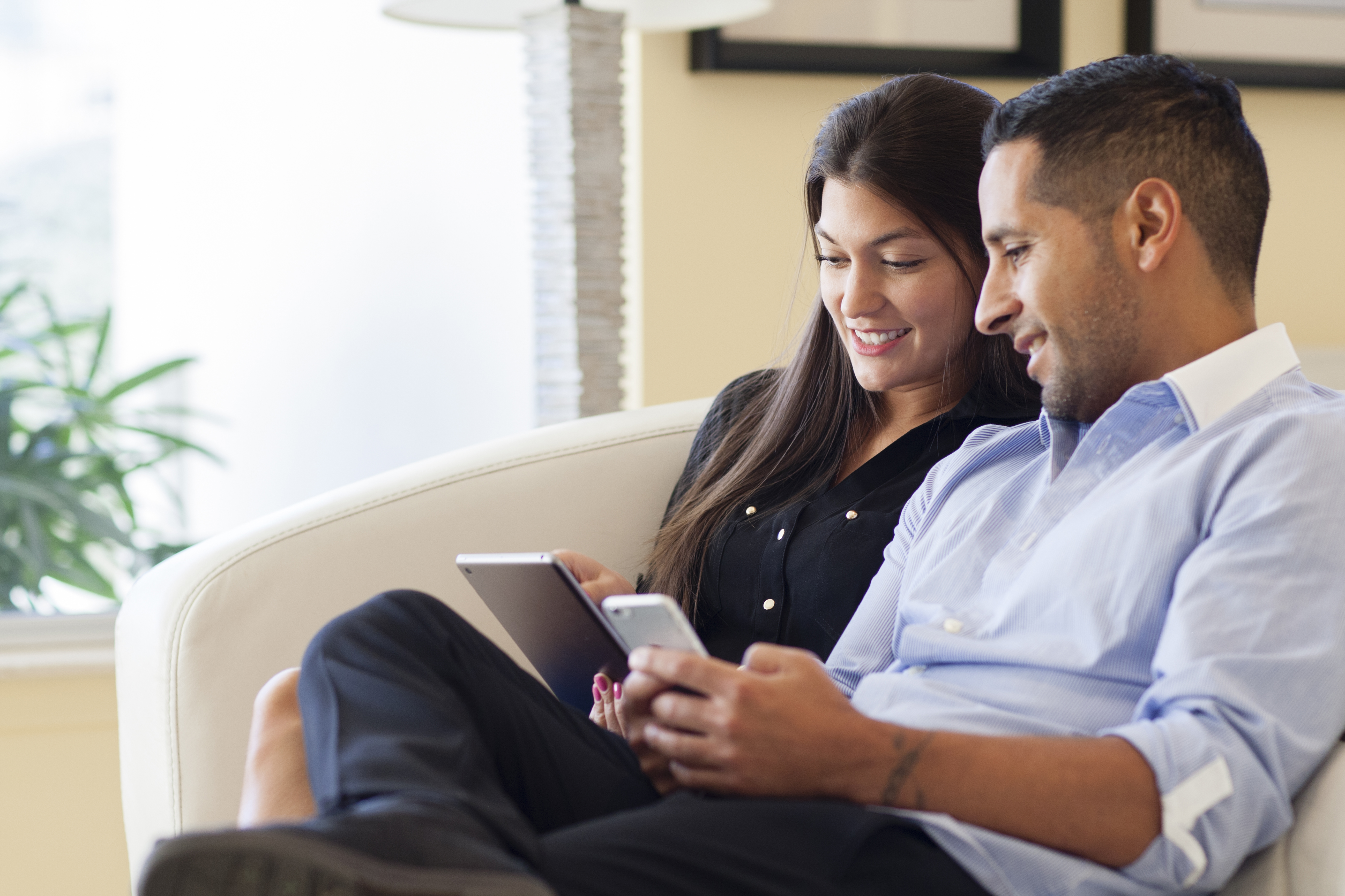 A couple looking through their phone and tablet