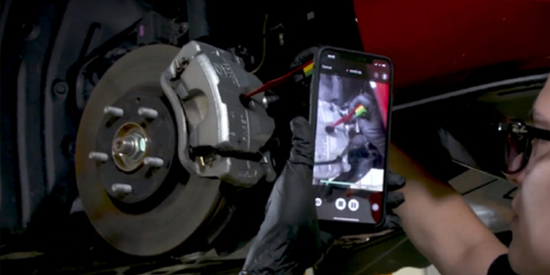 A man fixing his vehicle by following a video on his smart phone
