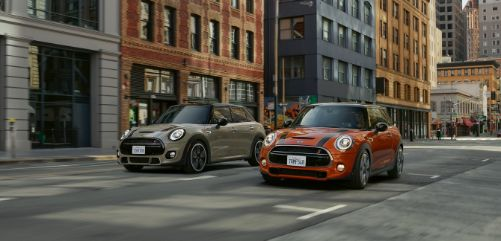 Two MINI's driving down the street