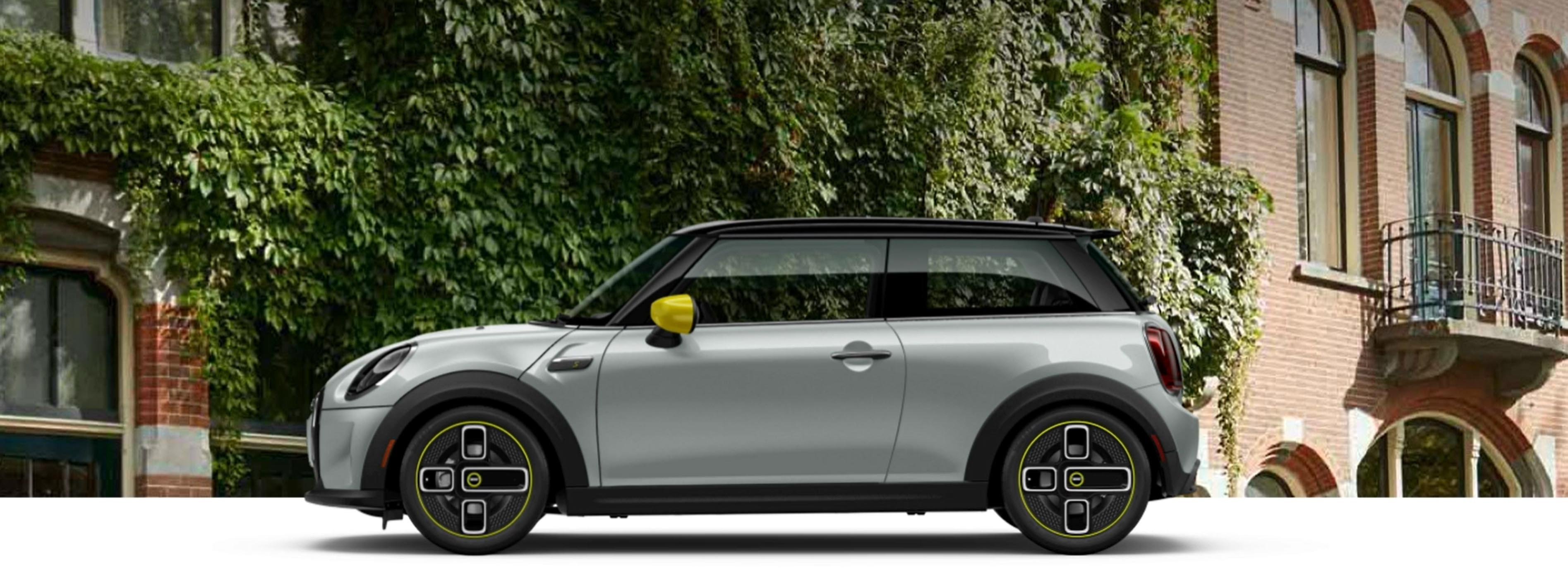 A 2022 MINI Cooper SE Hardtop 2 Door parked. in front of a brick building