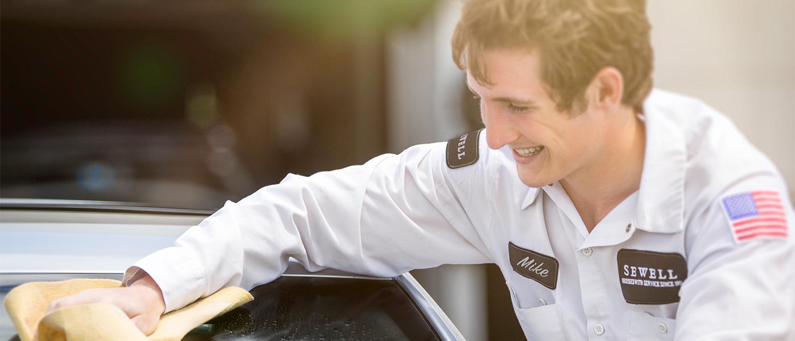 Sewell employee washing a car